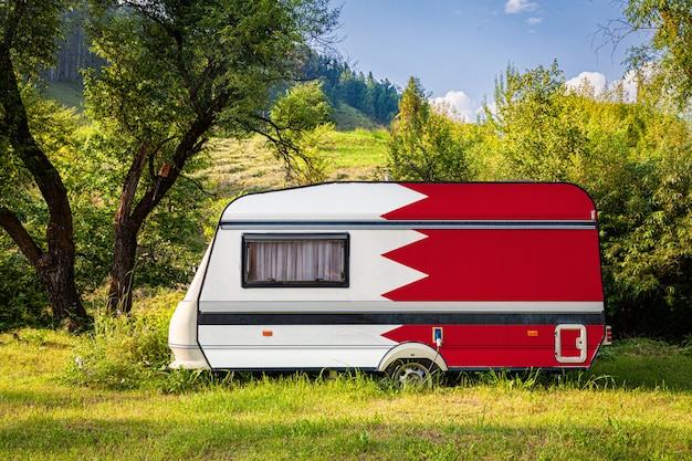 Автоприцеп, дом на колесах, окрашенный в национальный флаг бахрейна, стоит на стоянке в гористой местности.