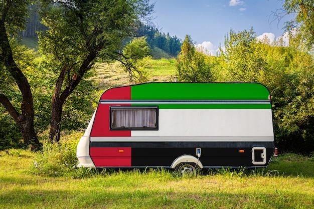 Автомобильный прицеп, дом на колесах, окрашенный в национальный флаг объединенных арабских эмиратов, стоит в гористой местности.