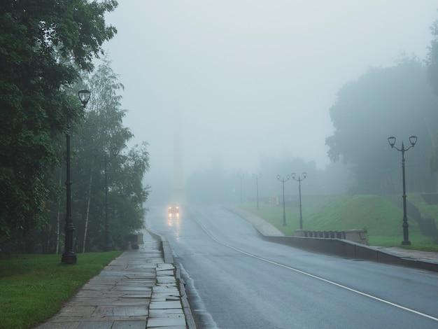 추운 아침에 안개가 자욱한 도로에 불이 켜진 자동차