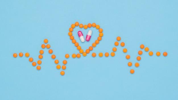 알약과 캡슐이있는 심장의 제품. 심장 질환 치료의 개념.