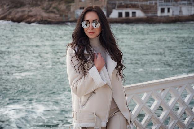 따뜻하고 바람이 부는 날에 바다의 전망을 즐기는 베이지색 옷을 입은 평온한 백인 여성. 아름다운 겨울날을 즐기고 바다 공기를 마시며 세련된 선글라스를 쓴 여성