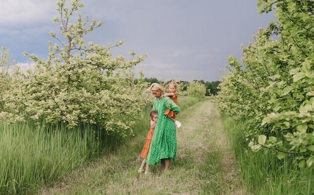 思いやりのある母親は、緑豊かな春の庭で小さな娘たちと遊んでいます。家族の喜び