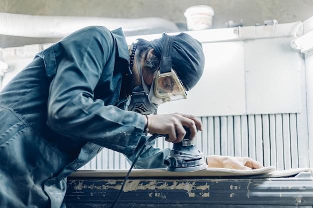 Плотник вырезает доску электрическим лобзиком. производство скейтбордов. у него есть защитная одежда и маска.