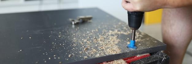 Плотник в мастерской проделывает отверстие в большом предмете мебели, руки мужчины держат специальный