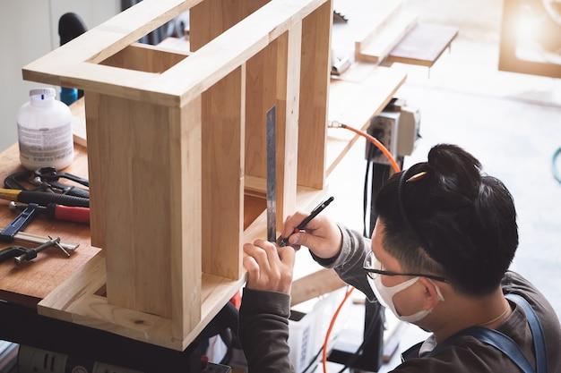 Плотник измеряет доски, чтобы собрать детали и построить деревянный стол для клиента.