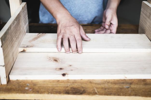 목수가 판자를 측정하여 부품을 조립하고 고객을 위해 나무 테이블을 만듭니다.