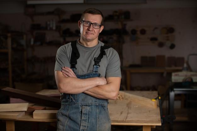 大工が腕を組んで木工所に立つ