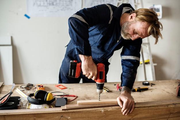 Плотник с помощью дрели по дереву