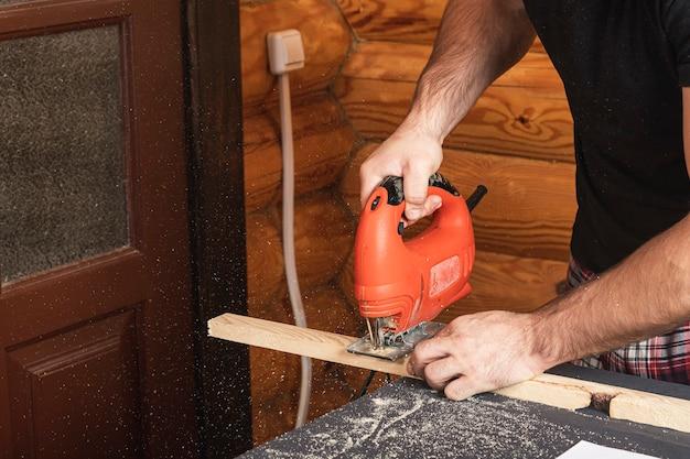 ジグソーを使って木を切る大工が棒を切ります。家の修理の概念、クローズアップ。