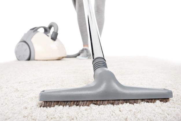 흰색 배경 위에 진공 청소기로 청소되는 카펫