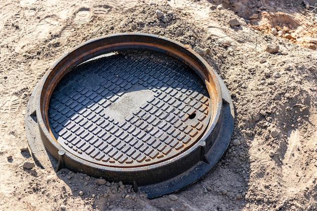 Подготовленный к установке чугунный канализационный люк. крупный план. дорожные работы. укрытие для подземных коммуникаций.