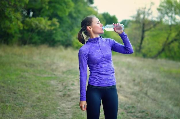 후드와 검은 색 레깅스와 파란색 스포츠 재킷에 백인 운동 여자는 화려한 녹색 숲 언덕에 조깅 후 병에서 물을 마신다.