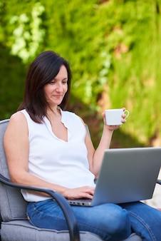 백인 브루네트 여성이 노트북 작업을 하는 동안 커피 한 잔을 들고 있다