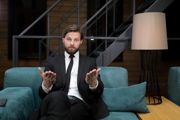 Кавказский бизнесмен в костюме и галстуке, улыбаясь в камеру, разговаривает во время онлайн-бизнес-конференции, объясняя детали контракта иностранному партнеру через приложение для подключения