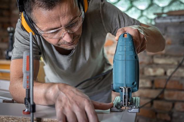 白人の大工は、彼のワークショップでジグソーパズルで木を切ることに集中しています。
