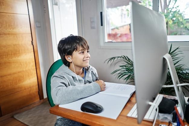 Кавказский ребенок учит дома по видеоконференции.