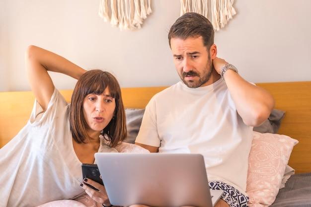 Кавказская пара на кровати с компьютером и телефоном, делает заказ в гостинице или на рейс, организует отдых, новые технологии в семье. с сомнением какую поездку выбрать
