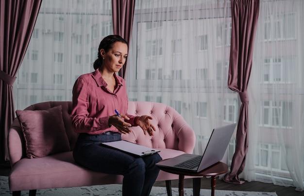 분홍색 셔츠를 입은 백인 여성 심리학자가 소파에 앉아 노트북으로 온라인 상담을 한다