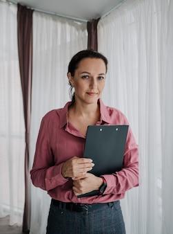 Кавказская женщина-психолог в розовой рубашке стоит у окна и смотрит в камеру
