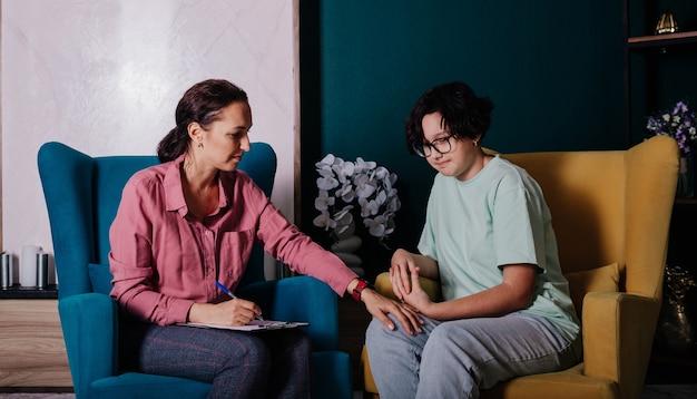 백인 여성 심리학자가 의자에 앉아 십대 소녀의 환자를 받고 있다