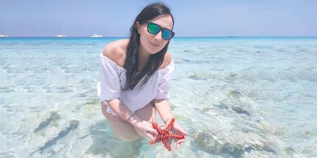 검은 머리에 선글라스와 흰색 선드레스를 입은 백인 소녀와 불가사리를 손에 들고 바다의 푸른 물을 배경으로 카메라를 바라보고 있습니다. 여행 개념입니다.