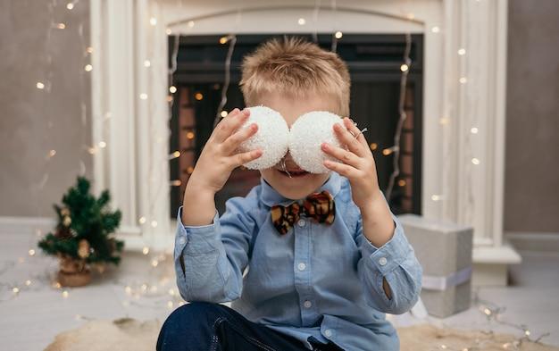 蝶と青いシャツを着た白人の小さな男の子は、クリスマスボールで目を閉じました