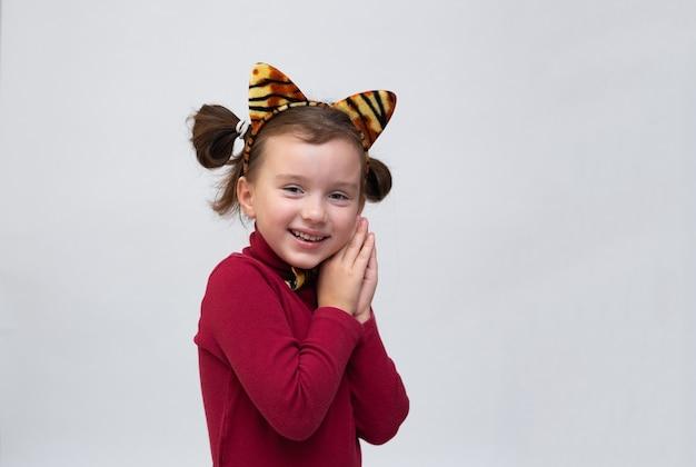 버건디 터틀넥을 입고 흰색 배경에 호랑이 귀가 달린 테두리가 있고 텍스트를 위한 장소가 있는 백인 소녀