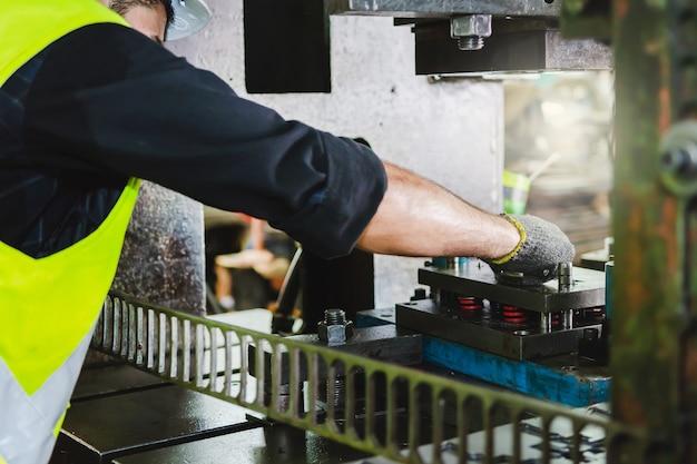 Кавказский инженер-механик проверяет станок на предмет металлоконструкций на заводе. инженер в каске работает на станке в слесарной промышленности.