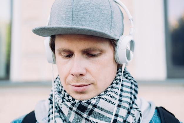 회색 모자에 백인 남자는 음악을 듣고 슬프다