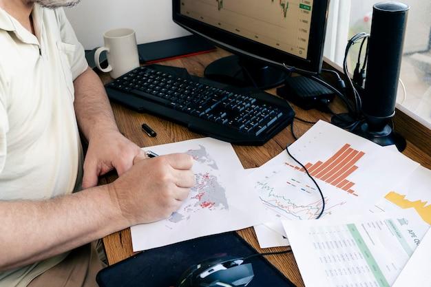 地図、チャート、グラフで論文を勉強している白人男性。