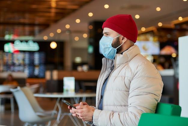 モールでスマートフォンを使用して顔にサージカルマスクを付けた白人男性。