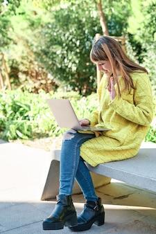 Кавказская симпатичная молодая девушка, одетая в желтый пиджак, белый свитер, проводит видеоконференцию с ноутбуком, сидя на скамейке в парке