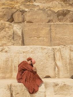 빨간 드레스와 모자를 쓴 백인 여성이 기자의 아름다운 카프레 피라미드에 앉아 있다