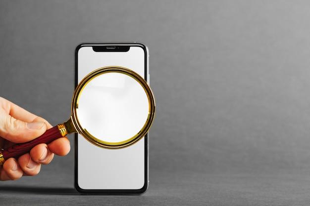 灰色の背景の広告のために手に携帯電話のタブレット