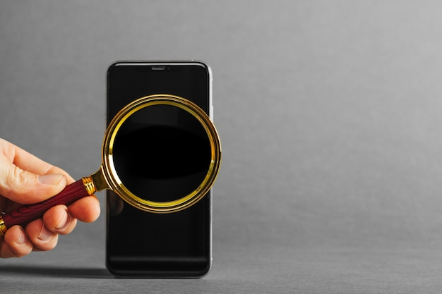 회색 표면에 광고를 위해 손에 휴대 전화 태블릿