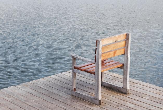 川沿いの桟橋にある椅子。孤独、穏やかな静けさと沈黙の最小限の概念