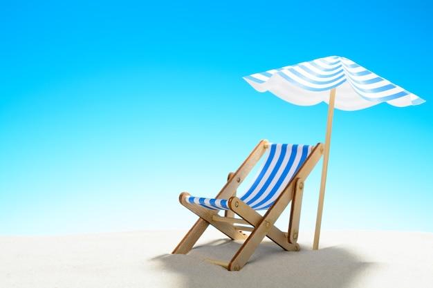 모래 해변에 우산 아래 긴 의자, 복사 공간이있는 하늘