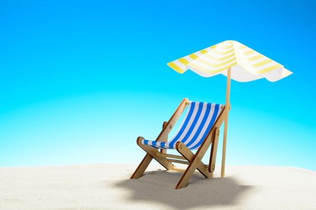 모래 해변에서 우산 아래 긴 의자