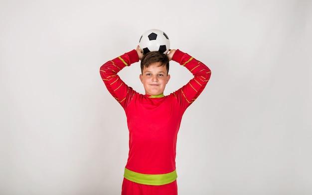 빨간 유니폼을 입은 챔피언 축구 선수는 텍스트를 위한 장소가 있는 흰색 배경에 축구공을 들고 서 있다