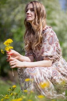 鮮やかな花と軽いドレスを着た魅力的なブロンドが咲くフィールドに座っています。