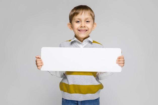 Очаровательный мальчик в белой рубашке, майке в полоску и светлых джинсах стоит на сером. мальчик держит белый прямоугольный плакат