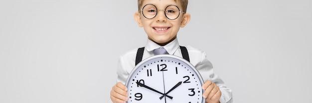 Очаровательный мальчик в белой рубашке, подтяжках, галстуке и светлых джинсах стоит на сером фоне. мальчик держит часы