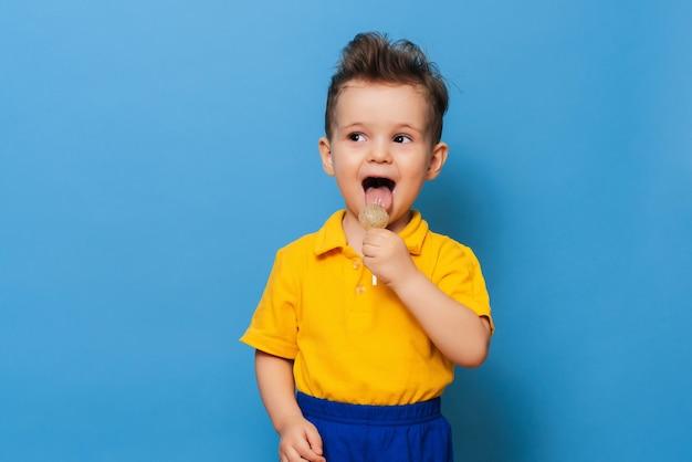 Очаровательный мальчик смотрит в камеру, держа леденец на синем фоне. профилактика детского кариеса
