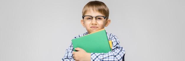 У очаровательного мальчика с вклетчатой рубашкой и светлыми джинсами стоит серый. мальчик держит в руках разноцветную папку с документами