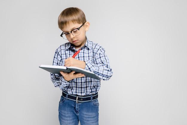 Очаровательный мальчик с вклетчатой рубашкой и светлыми джинсами стоит на сером. мальчик держит в руках блокнот и ручку.
