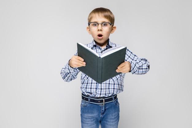 Очаровательный мальчик с инкрустированной рубашкой и светлыми джинсами стоит на сером фоне. мальчик держит в руках книгу. мальчик в очках