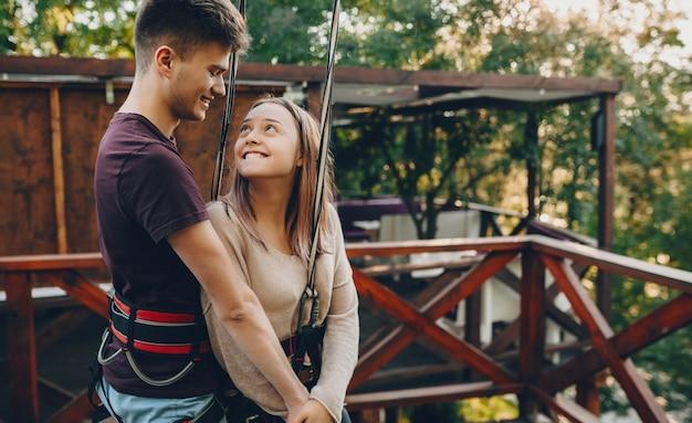 彼女の恋人の目に自信を探している魅力的な白人女性は彼の手を握って無邪気に笑っています