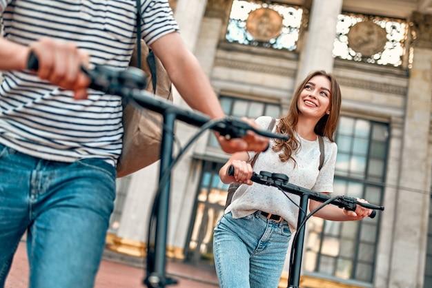 Очаровательная девушка и привлекательный парень на электросамокатах. пара студентов на скутерах возле кампуса.
