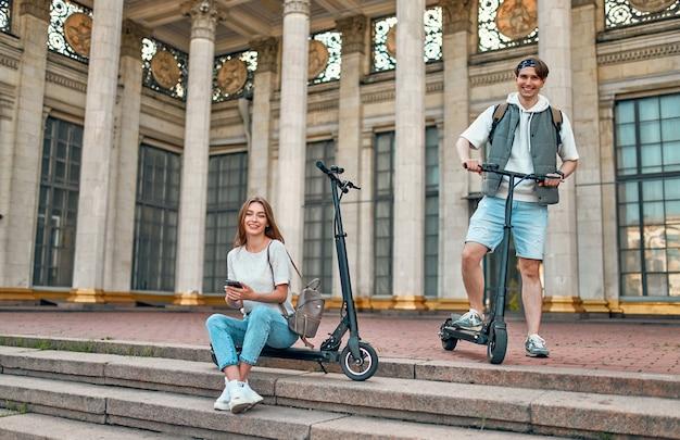 スマートフォンで電動スクーターに乗っている魅力的な女の子と魅力的な男。キャンパス近くのスクーターに乗っている数人の学生。