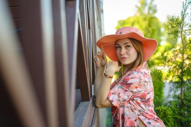 Очаровательная девушка в легком летнем сарафане и шляпе-парео гуляет по зеленому парку. любит теплые солнечные летние дни.